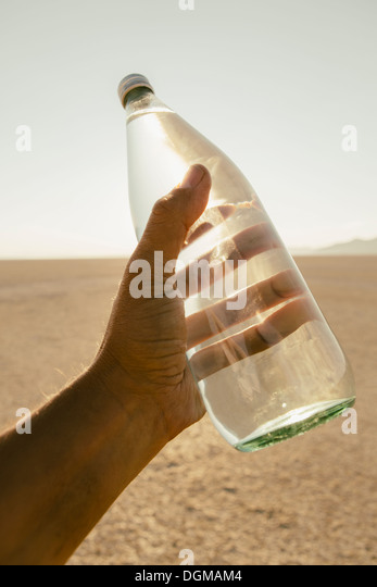 The landscape of the Black Rock Desert in Nevada. A man's hand holding a bottle of water. Filtered mineral water. - Stock Image
