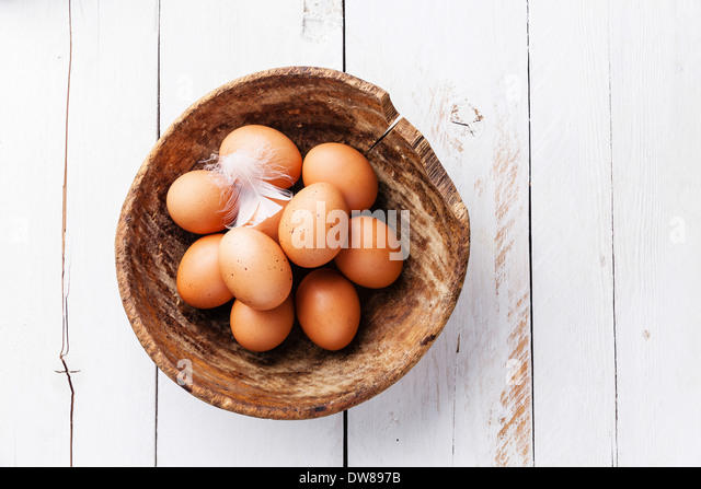 Eggs in bowl on wooden background - Stock Image