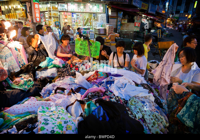 Korean women shopping at stall selling clothing in Namdaemun market in Seoul South Korea at dusk. JMH3855 - Stock Image