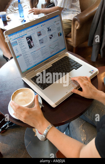 Young woman browsing the internet on a laptop computer in a coffee shop, England UK - Stock-Bilder