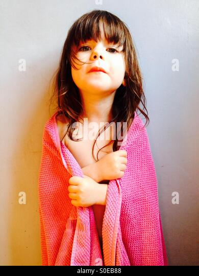 3-year old girl wrapped in towel after bath - Stock-Bilder