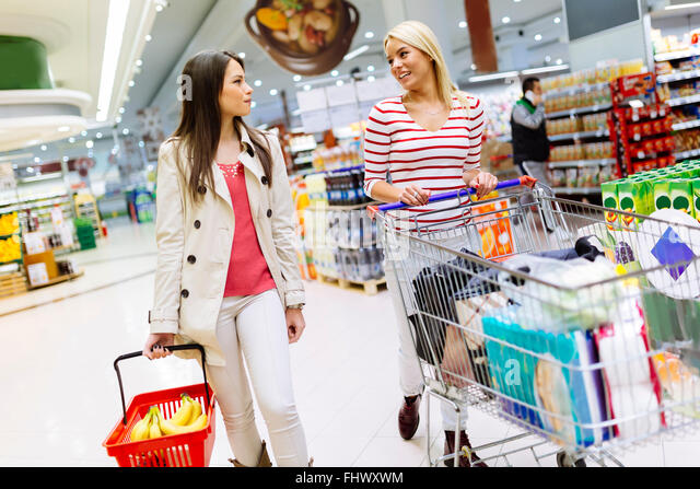Two beautiful women shopping in supermarket - Stock Image