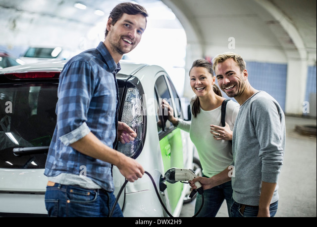 Portrait of happy friends with man charging electric car at gas station - Stock Image