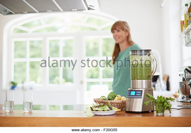 Woman next to blender full of green vegan smoothie - Stock Image