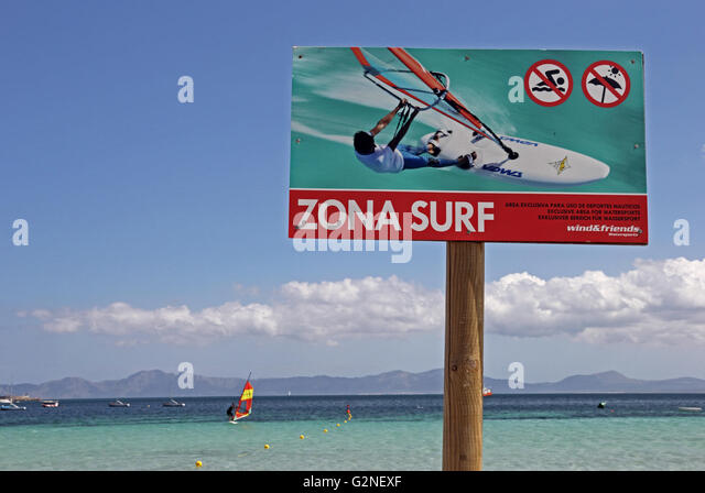 Zona Surf, sign indicating area reserved for wind surfing, with windsurfer in background - Stock Image