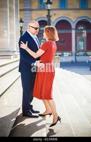 Senior couple embraces on staircase outdoors, Munich, Bavaria, Germany - Stock-Bilder