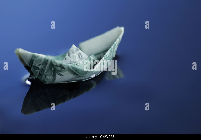 Origami boat made of dollar bill afloat - Stock Image