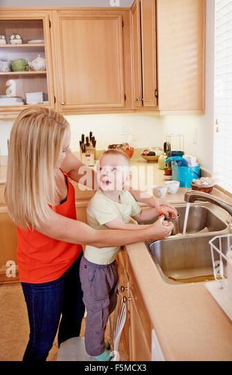 Mother washing son's hands in kitchen sink - Stock-Bilder