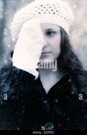 a woman in a black coat with a white cap is holding a gloved hand in front of one of her eyes - Stock Image