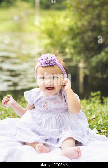 Full Length Of A Pretty Baby Girl Sitting By The Lake - Stock Image