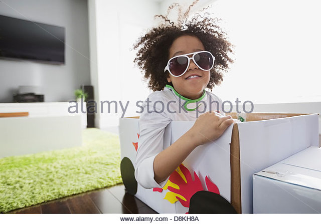 Portrait of boy pretending to be race car driver at home - Stock Image