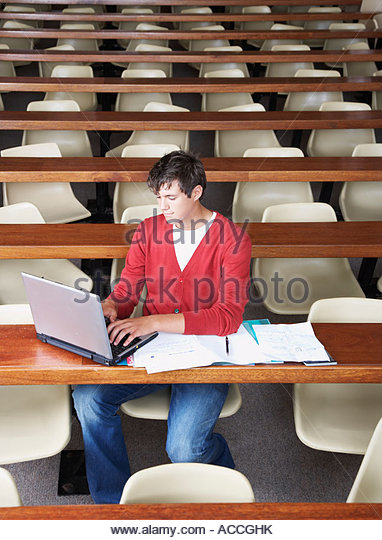 A young male student sitting in a classroom on a laptop - Stock Image