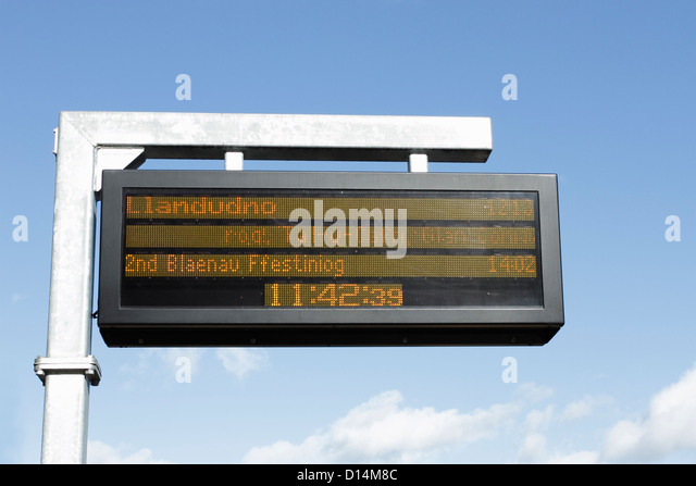 Train arrivals and departure times being shown on an electronic notice board on a railway station platform. - Stock-Bilder