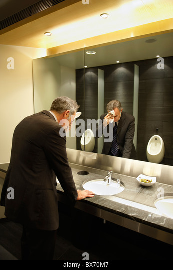Anxious businessman in front of mirror in restroom/public toilet - Stock Image