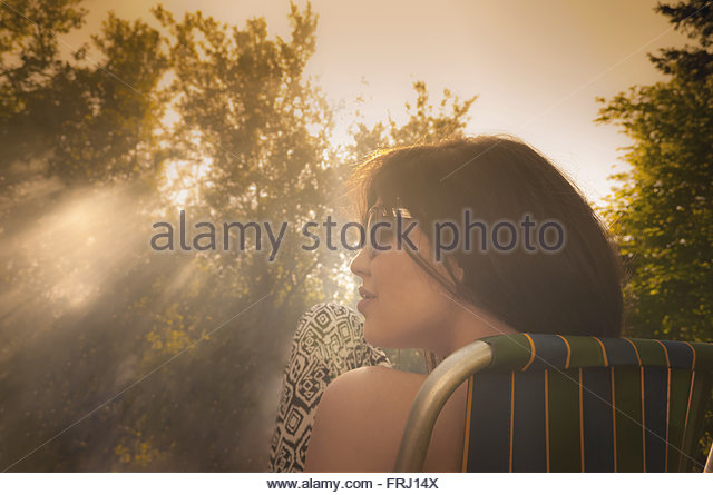 Girl enjoying hazy sunshine in morning - Stock-Bilder