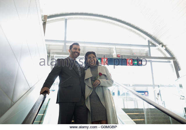 Smiling couple descending escalator at train station - Stock Image