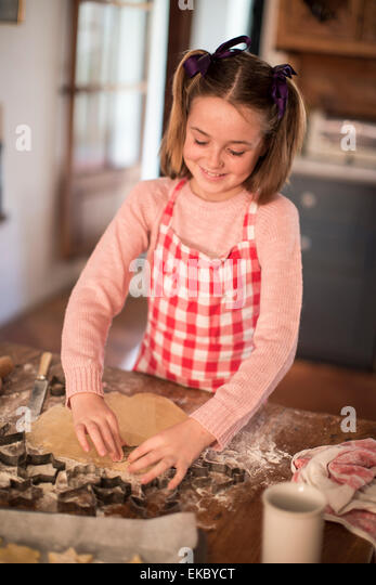 Girl cutting shapes in dough to make homemade cookies - Stock Image