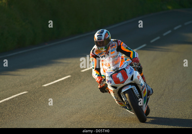 A photograph of John McGuinness approaching the 'Gooseneck' during the 2012 TT, on the Padgetts MMCG Superstock - Stock Image