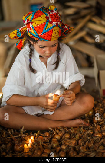 Portrait of girl sitting on pile of onions holding onion bulb - Stock Image