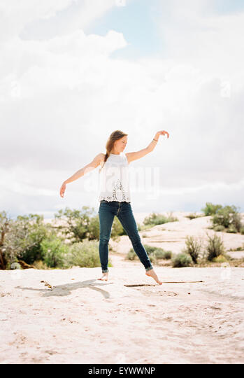 Barefoot woman wearing jeans her arms raised. - Stock Image