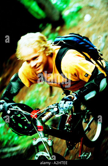 male age 20-25 riding a mountain bike through the woods.The Image shows movement and is in color. - Stock Image