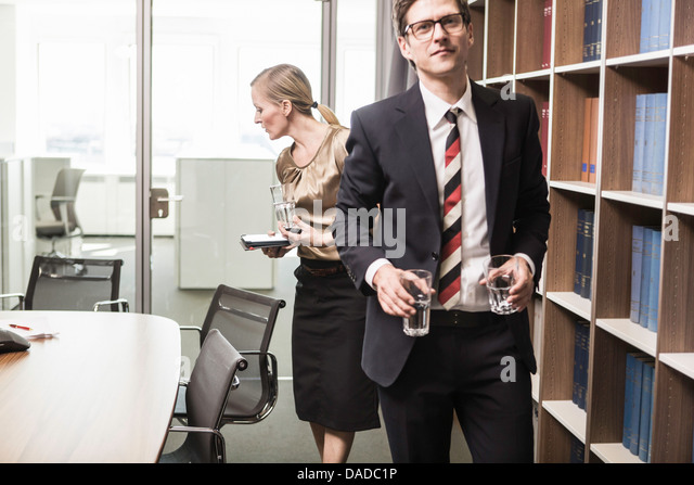 Lawyer leaving meeting room with drinking glasses - Stock-Bilder