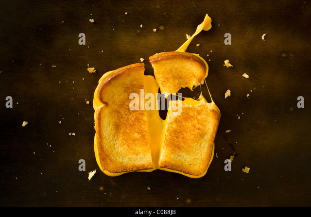 A Grilled Cheese Sandwich cut in half and with the top right corner broken off pulling the cheese on a wood table - Stock Image