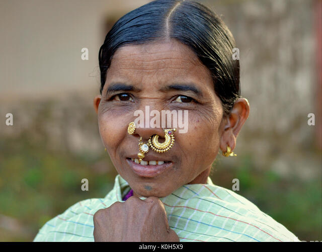 Elderly Indian Adivasi market woman with precious golden nose studs/rings/jewellery and tribal earrings. - Stock Image