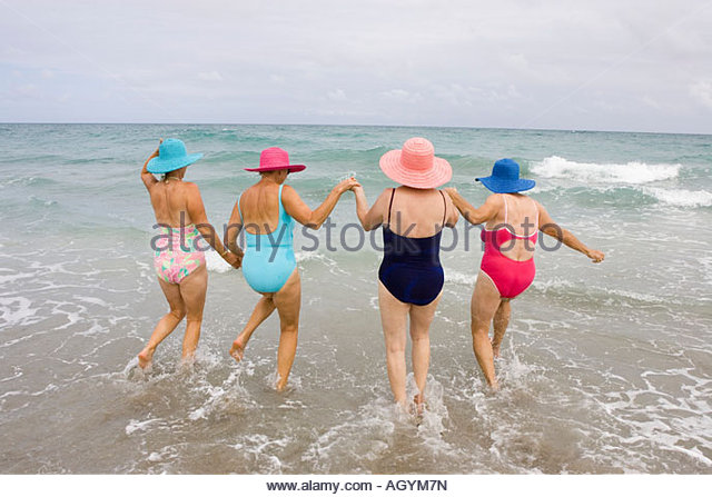 Rear view of four senior woman wading in surf - Stock Image