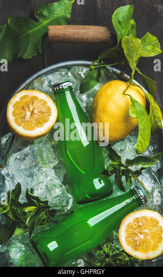 Bottles of green lemonade on chipped ice in metal tray - Stock Image