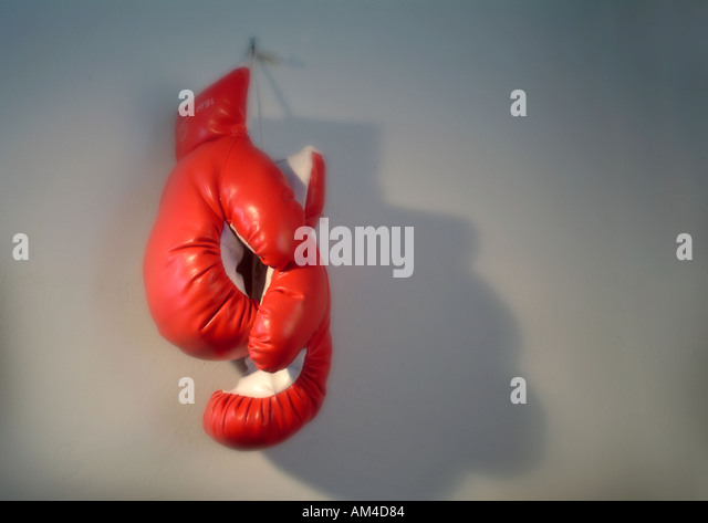 Boxing Gloves hang on a wall as a metaphor for retirement or the expression - Hang up the gloves - Stock Image