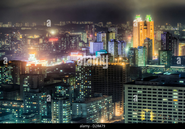 New modern buildings in the centre of Pyongyang colourfully illuminated at night, Pyongyang, North Korea - Stock Image