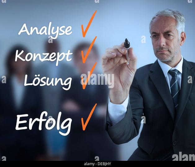 Businessman writing a success checklist in german - Stock-Bilder