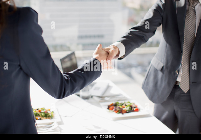 Businessman and businesswoman shaking hands at table with lunch - Stock Image
