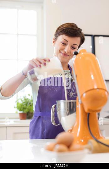 Smiling woman baking, using stand mixer in kitchen - Stock-Bilder