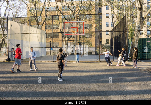 teen black girl aims for the basket in a good natured unisex pick up basketball game in DeWitt Clinton park Hells - Stock Image