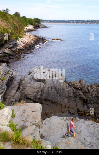 Rhode Island Newport Easton Bay Cliff Walk rocky coast shoreline woman exploring - Stock Image