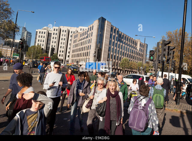 A crowd of people crossing the road at a pedestrian crossing, Tower Hill, London UK - Stock Image
