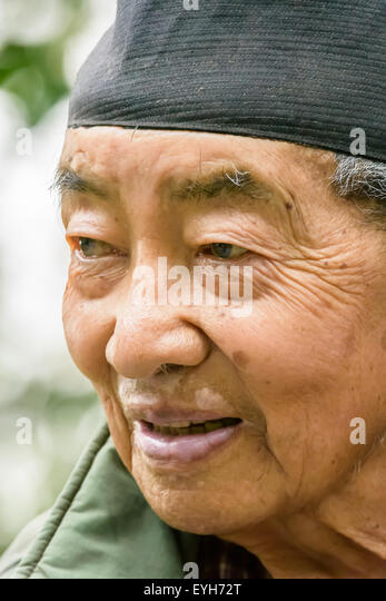 Portrait of an happy old nepali man mongoloid character with cap on head and gray hair and wrinkled face - Stock Image
