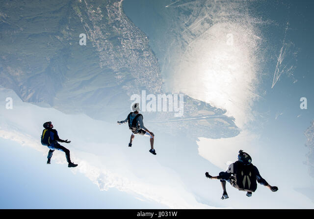 Three skydivers tracking above Locarno, Switzerland with the alps in the Background - Stock Image