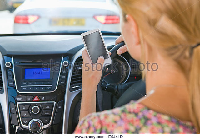 Female Driver Sending Text Message Whilst Driving - Stock Image