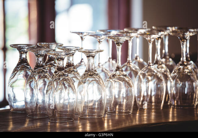 Empty wine glasses arranged on bar counter - Stock Image