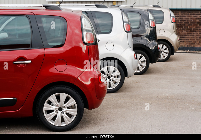 row of new cars for retail sale in a motor dealer yard showing same model in different color choices - Stock Image