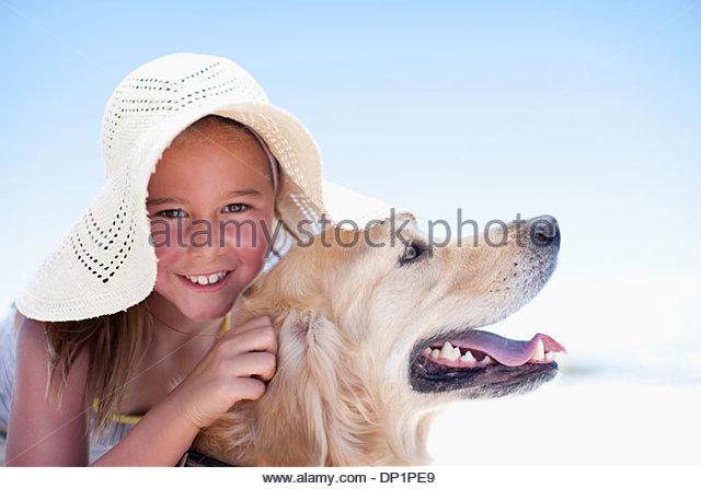 Girl hugging dog on beach - Stock Image