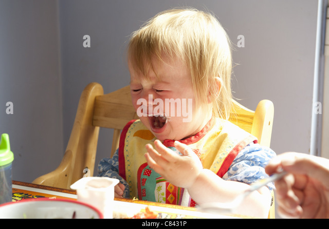 Toddler girl crying at table - Stock Image