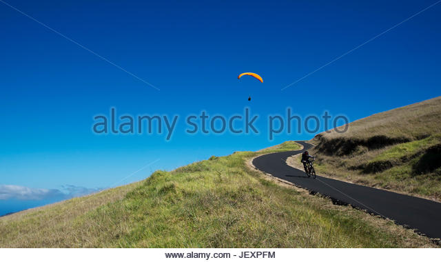 A paraglider soars above a mountain biker. - Stock Image
