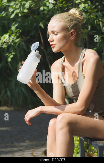 Young woman sitting outdoors with water bottle, eyes closed - Stock-Bilder