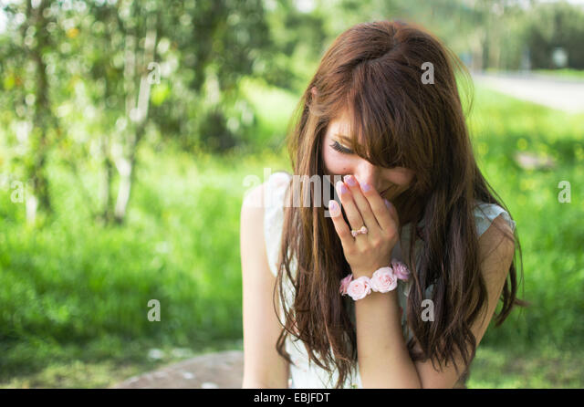Young woman outdoors, laughing - Stock Image