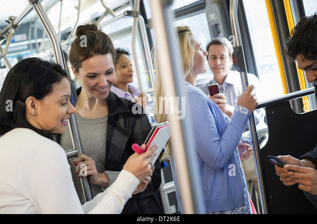 New York City People men and women on a city bus Public transport Two women looking at a handheld digital tablet - Stock Image