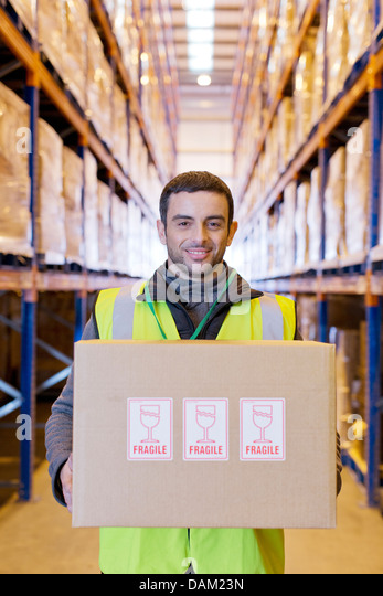Worker carrying 'fragile' box in warehouse - Stock Image